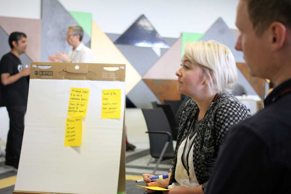 Woman looking at post-it notes on a whiteboard